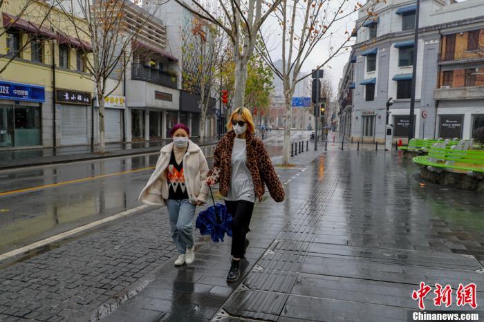 两位女市民戴着口罩行走在空旷的武汉中山大道上。中新社记者 张畅 摄
