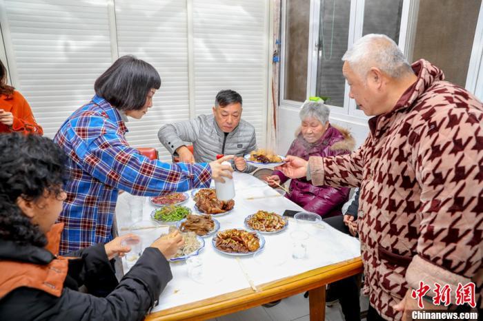 武汉市民叶先生一家吃年夜饭。中新社记者 张畅 摄
