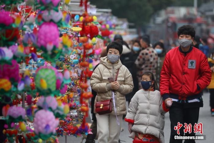 资料图:佩戴口罩的游客在南京夫子庙花灯市场游览。中新社记者 泱波 摄