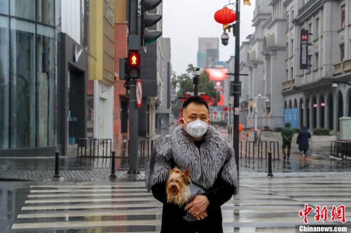 空旷的武汉江汉路步行街上,一位市民佩戴口罩带着宠物狗出行。中新社记者 张畅 摄
