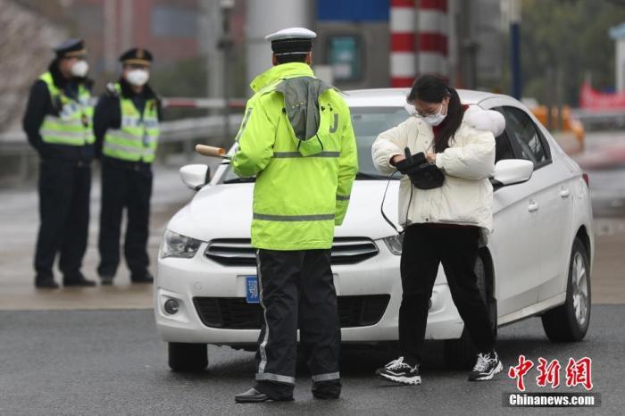 1月24日,京沪高速江桥收费站,一辆鄂牌照小汽车被交警拦下进行防疫检查。中新社记者 张亨伟 摄