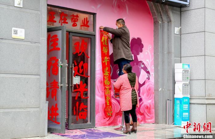 汉口江汉路步行街上,商家在贴春联。中新社记者 张畅 摄
