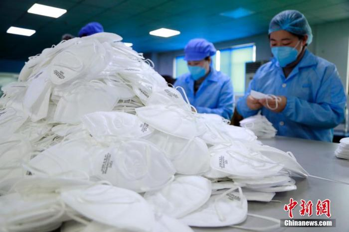1月24日,上海郊区奉贤一家专业生产KN95口罩的工厂内,工人加班加点生产口罩。新型冠状病毒感染的肺炎疫情扩散,防护口罩成为紧俏商品,市场需求陡然上涨,一时间供不应求。上海的口罩生产厂家,召回技术骨干和部分工人,并聘请临时工,春节假期开启全天候生产模式。劳作了一年的外来务工人员,或放弃与家人团聚,或从家中即刻返回。中新社记者 汤彦俊 摄