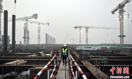 资料图:2020年1月15日,京雄城际铁路雄安站工作人员在40多米的平台上施工。<a target='_blank' >中新社</a>记者 韩冰 摄