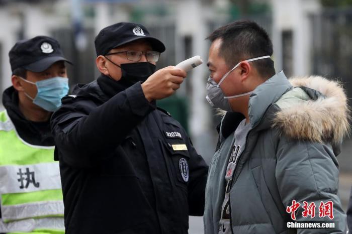 1月25日,南京门东老街入口处,工作人员对进入的民众进行体温测量。当日,江苏省启动突发公共卫生事件一级响应,加强新型冠状病毒感染的肺炎疫情防控工作,实行最严格的科学防控措施。中新社记者 泱波 摄