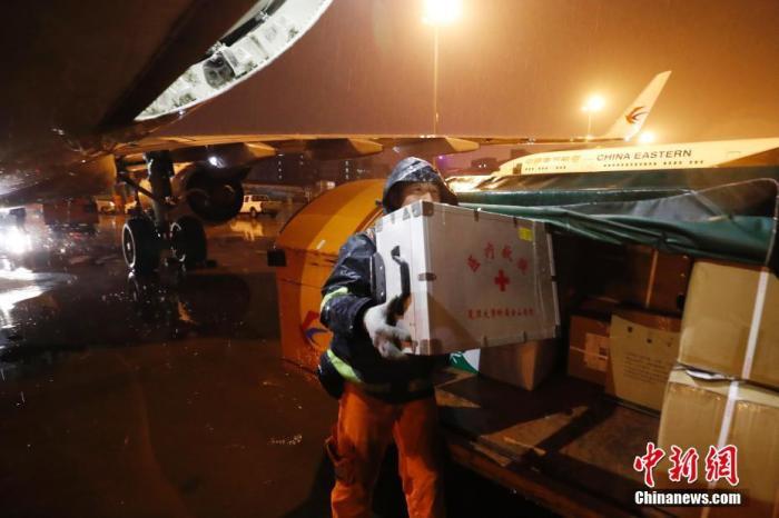 1月25日凌晨1时25分,大年初一,来自上海市28家市级医院和5个区近30家医院的136名医护人员,乘坐东航包机MU5000航班平安降落在武汉天河机场,支援湖北抗击新型肺炎。该航班也是民航首批执行驰援武汉任务的包机航班。图为工作人员冒雨搬运医疗物资。中新社记者 殷立勤 摄