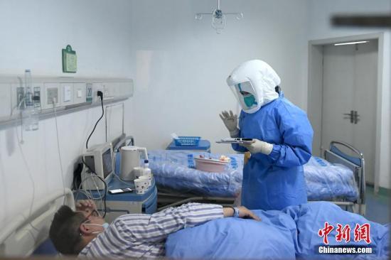 1月24日,农历大年三十,成都定点收治新型冠状病毒感染的肺炎患者的医院——成都市公共卫生临床医疗中心,不少医护人员正在走廊中间的护士站忙碌着。相比普通的住院病房,这里只有医疗设备运转的嗡嗡声,显得十分安静,医护人员们正细心地照顾着每一位患者。图为医护人员在和患者交流。安源 摄