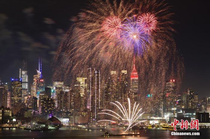当地时间1月23日晚,纽约哈德逊河上空燃放焰火、帝国大厦点亮红色彩灯,庆祝中国春节。中新社记者 廖攀 摄