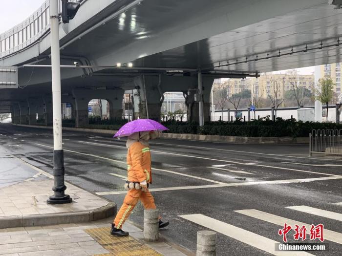 1月26日,农历大年初二,武汉市汉阳区一名环卫工人过马路。武汉市新型肺炎防控指挥部25日发布第9号通告,为控制人员流动引发的传染风险,自2020年1月26日0时始,除经许可的保供运输车、免费交通车、公务用车外,中心城区区域实行机动车禁行管理。 <a target='_blank' href='http://www.chinanews.com/'>中新社</a>记者 杨程晨 摄