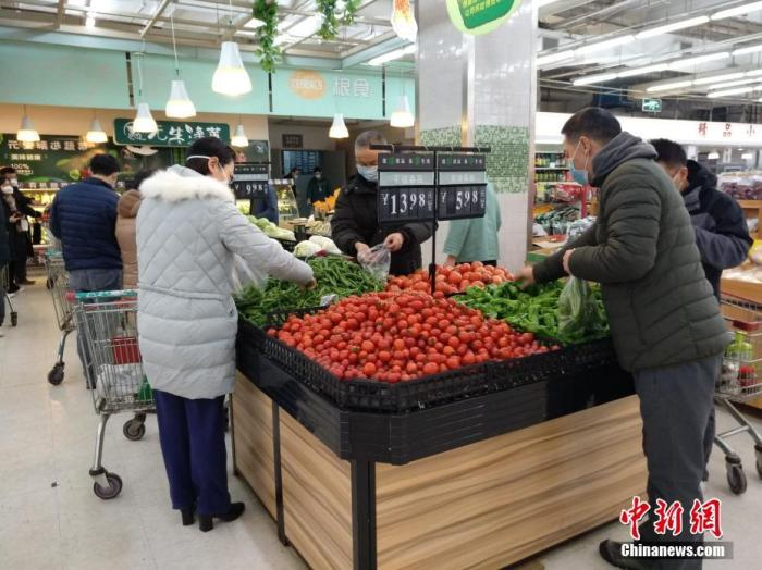 1月26日,农历大年初二,武汉超市内各种新鲜蔬菜供应充足,市民戴口罩选购。中新社记者 丁喆 摄