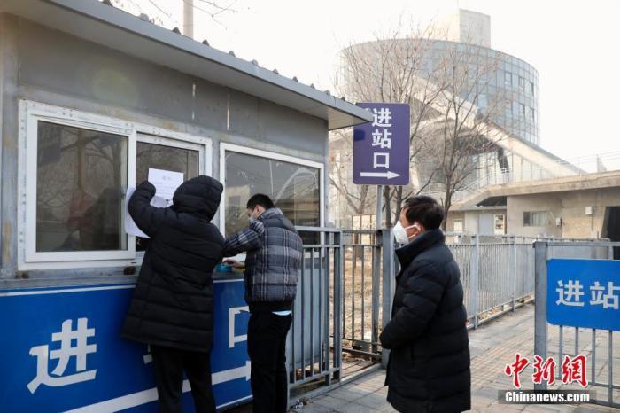 """1月26日,北京六里桥客运主枢纽的工作人员在车站进站口处张贴""""停运""""通知。北京市交通委26日发布消息,为严控新型冠状病毒通过道路客运传播,从1月26日起,除政府指定及疫情防控工作需要,暂停进出北京的经营性长途客运班线(不含跨市运营的地面公交线路)和旅游包车,恢复时间另行通知。乘客可免费退票。中新社记者 盛佳鹏 摄"""