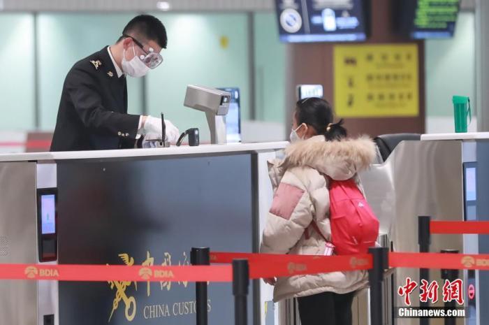 1月26日,受新型冠狀病毒感染的肺炎疫情影響,北京大興國際機場海關工作人員戴上口罩和護目鏡為旅客辦理相關手續。中新社記者 賈天勇 攝