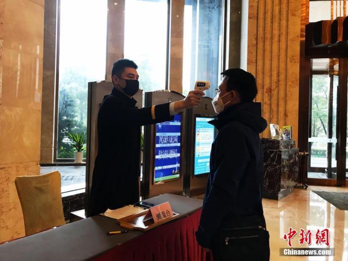 1月26日,武汉某酒店,工作人员坚守岗位并对进入酒店者测量体温。中新社记者 张芹 摄