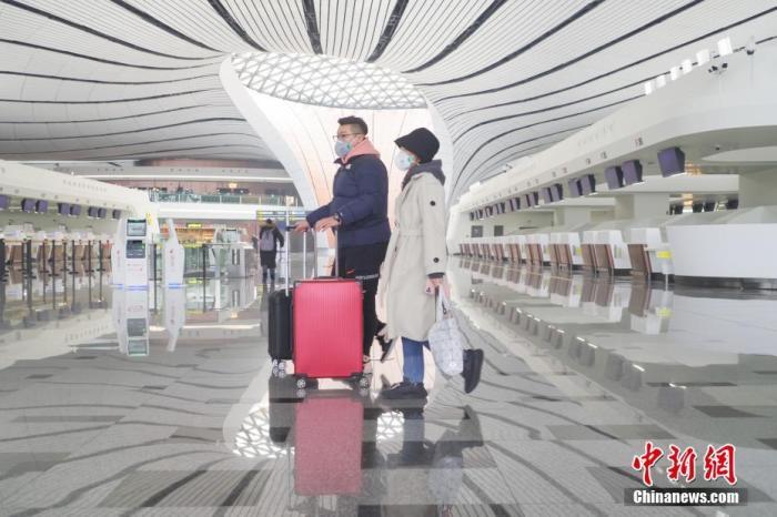 1月26日,受新型冠状病毒感染的肺炎疫情影响,北京大兴国际机场内,旅客戴口罩出行。<a target='_blank' href='http://www.chinanews.com/'>中新社</a>记者 贾天勇 摄
