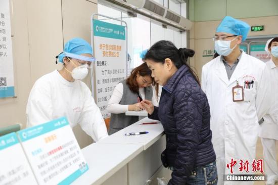 资料图:医护人员穿戴防护装备接诊。蓝飞燕 摄
