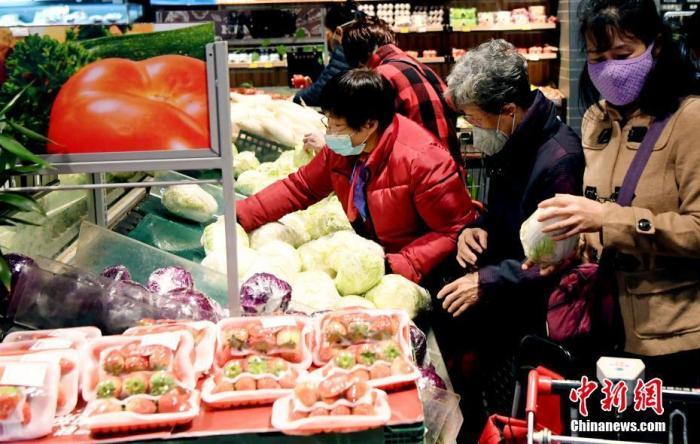 1月27日,夏历正月初三,在福州市区一家大型超市,市民戴口罩选购蔬菜。/p中新社记者 刘可耕 摄