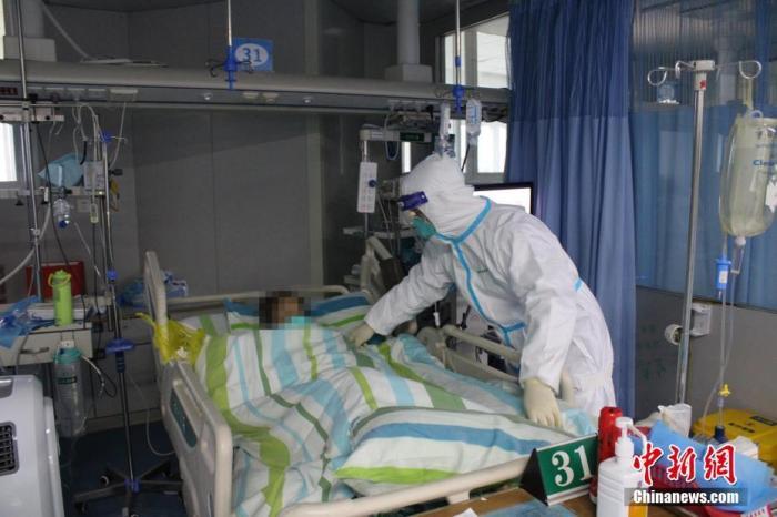 资料图:医护人员正在为新型冠状病毒感染的肺炎患者整理被褥。中新社记者 周群峰 摄