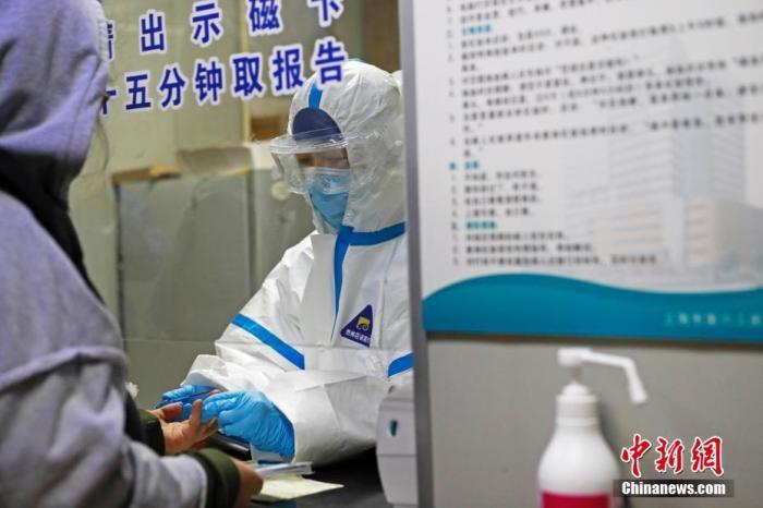 资料图:发热门诊医护人员正在对患者进行化验检查。中新社记者 殷立勤 摄