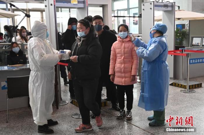 1月27日,受新型冠状病毒感染的肺炎疫情影响,安徽蚌埠南站大发欢乐生肖人员为旅客进行体温检测。中新社记者 张兴龙 摄