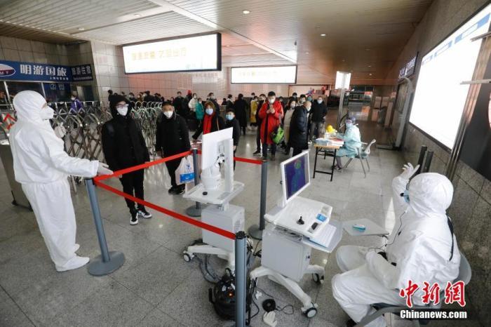 1月26日,旅客在上海站出站口排队等待体温检测。为防控新型冠状病毒感染的肺炎疫情,上海铁路方面采取了在上海、上海虹桥、上海南、上海西、安亭北、南翔北出站口设置测温点,对抵达上海的旅客全部进行体温检测。中新社记者 殷立勤 摄