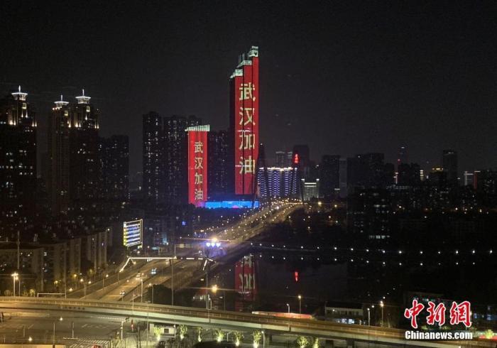 """1月28日,武汉市汉江边上的两栋建筑亮起""""武汉加油""""字样霓虹灯。<a target='_blank' href='http://www.chinanews.com/'>中新社</a>记者 杨程晨 摄"""