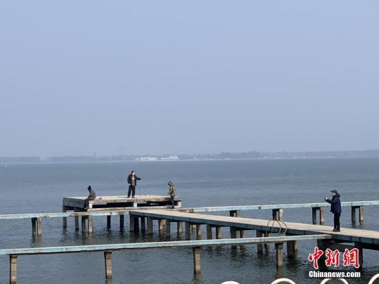 1月29日,一些市民來到位于武漢大學凌波門外的東湖棧橋上,佩戴口罩曬太陽。 <a target='_blank' href='http://www.jylmpo.tw/'>中新社</a>記者 楊程晨 攝