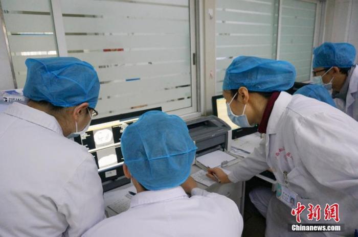 1月30日,记者实地探访位于广西桂林的广西壮族自治区南溪山医院感染性疾病科住院部,该医院是广西壮族自治区新型冠状病毒感染的肺炎定点收治医院之一。图为医务人员在分析患者病情。 中新社记者 欧惠兰 摄
