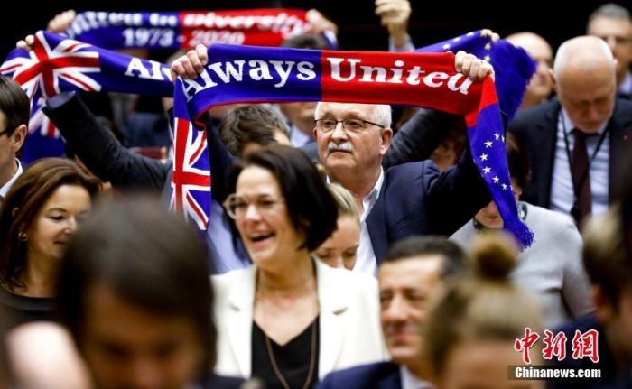 """资料图:当地时间1月29日,欧洲议会批准""""脱欧""""协议。图为投票结束后,在场议员高举""""永远团结""""旗帜。中新社发 欧盟供图"""