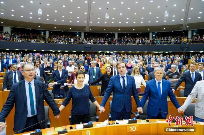"""当地时间1月29日,欧洲议会批准""""脱欧""""协议。投票结束后,在场议员手拉手唱起苏格兰经典歌曲《友谊地久天长》,以这首家喻户晓的""""离别之曲""""送别英国。中新社发 欧盟供图"""