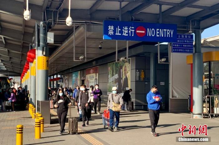 1月30日下午,有不少香港市民经由深圳湾口岸返回香港,而大人小孩均戴上口罩乘坐跨境直通巴士过境。中新社记者 李志华 摄