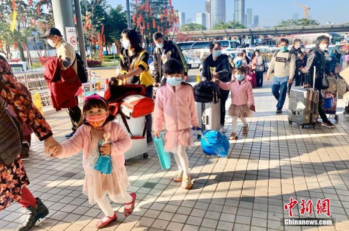 资料图:大人小孩戴上口罩从深圳湾口岸过境,以防受到感染。<a target='_blank' href='http://www.chinanews.com/'>中新社</a>记者 李志华 摄