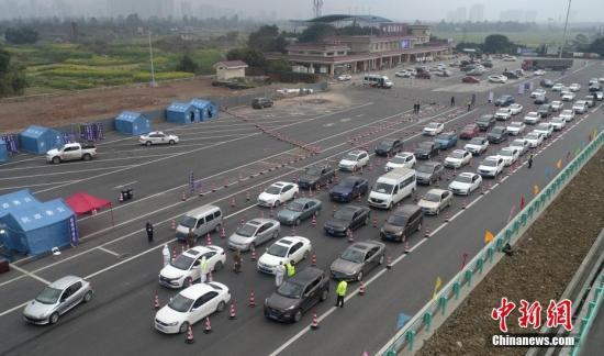 资料图:2月1日,检疫人员在四川眉山一高速公路服务区设专用通道,对驾乘人员逐一测量体温。中新社记者 刘忠俊 摄