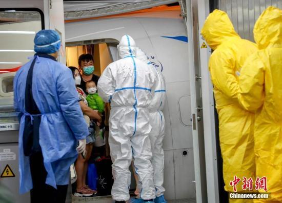 1月31日晚,一架自泰国曼谷起飞载有76名武汉游客的厦门航空航班,平稳地降落在武汉天河机场。这是中国政府决定尽快派民航包机直接接回尚在海外湖北公民后,武汉天河机场迎来的首批搭乘包机自国外返程旅客。图为旅客排队走出机舱。 中新社记者 张畅 摄