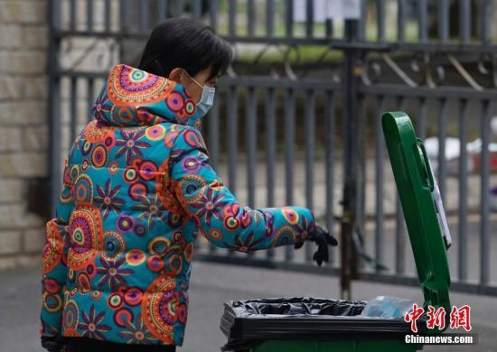 2月1日,贵州省贵阳市的一处居民小区院内,一名市民将用过的口罩投入专用收集箱内。据了解,该小区物业管理方设置了废弃口罩专用收集箱,并提示了丢弃口罩的正确方法。 中新社记者 侯宇 摄