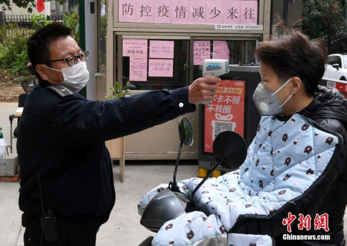 资料图:一住宅小区安防人员为进出人员检测体温。 中新社记者 刘可耕 摄