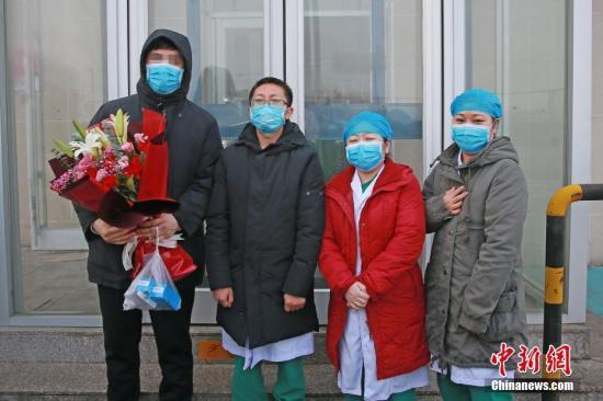 资料图:2月2日,在天津海河医院,天津首例新型冠状病毒感染的肺炎患者治愈出院。图为治愈患者(左一)与医护人员合影。 <a target='_blank' href='http://www.chinanews.com/'>中新社</a>发 钟欣 摄