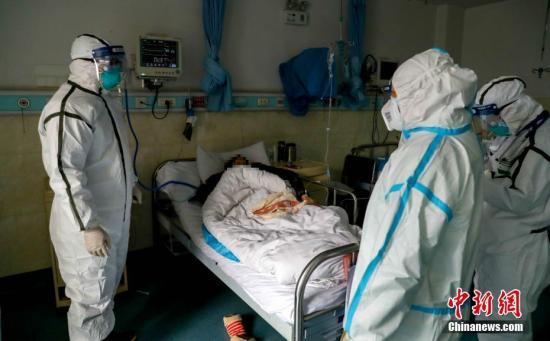 2月3日,医院隔离病房内,医务人员查房。中新社记者 张畅 摄