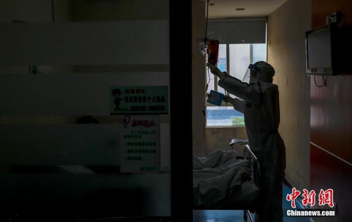 2月3日,武汉一医院隔离病房内,一名护士在为患者打针。中新社记者 张畅 摄