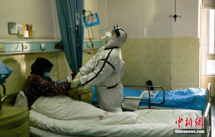 2月3日,医院隔离病房内,一名医务人员在为患者打针。中新社记者 张畅 摄