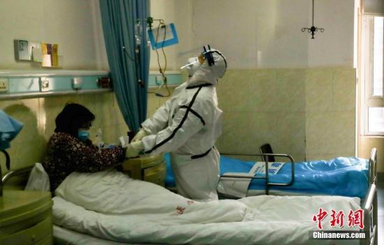 资料图:医院隔离病房内,一名医务人员在为患者打针。 中新社记者 张畅 摄
