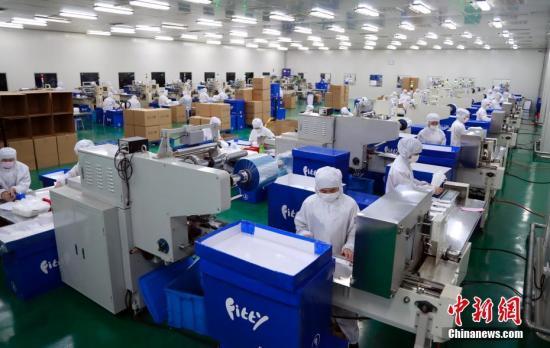 新型冠状病毒肺炎疫情发生以来,口罩成为全国最为稀缺的资源之一。2月4日,在上海玉川卫生用品公司,工人们正在加班加点赶制口罩。汤彦俊 摄