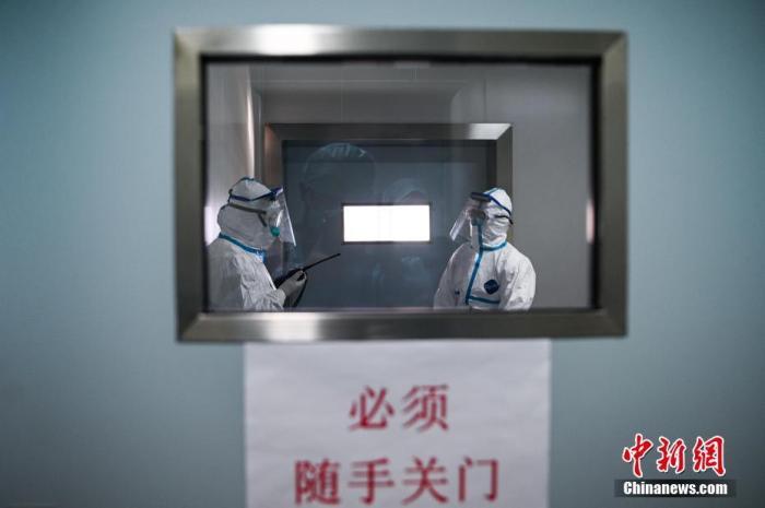 医院隔离病房内,医务人员查房。中新社记者 何蓬磊 摄