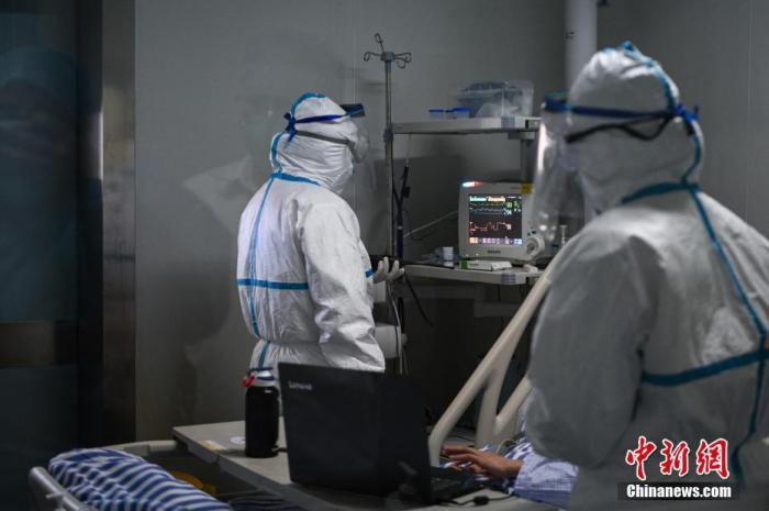 身着防护服的医务人员为患者做常规检查。中新社记者 何蓬磊 摄