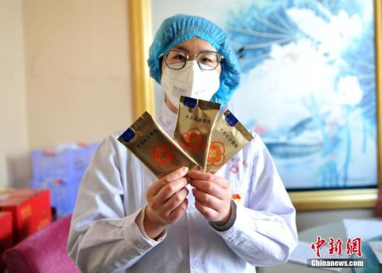 资料图:医护人员展示根据《新型冠状病毒感染的肺炎诊疗方案》研制的中药制剂。/p中新社记者 韩冰 摄