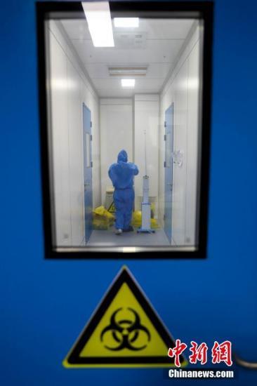 """2月4日,武汉市疾控中心检测组工作人员进行病毒检测。武汉市疾控中心是该市首批获准开展新型冠状病毒核酸检测的机构之一。位于该中心病原生物检验所的生物安全二级实验室(P2实验室)则是""""绝对禁区""""。图为武汉市疾控中心的P2实验室的工作人员在换装。<a target='_blank' href='http://sjzjysm.com/'>中新社</a>记者 张畅 摄"""