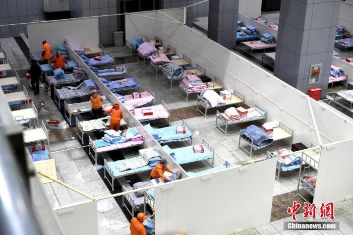 """2月4日晚,武汉市国际会展中心""""方舱医院""""里,施工人员仍在现场进行水电、木工等工程施工,环卫工人们正在现场装订床铺、整理被套。安源 摄"""