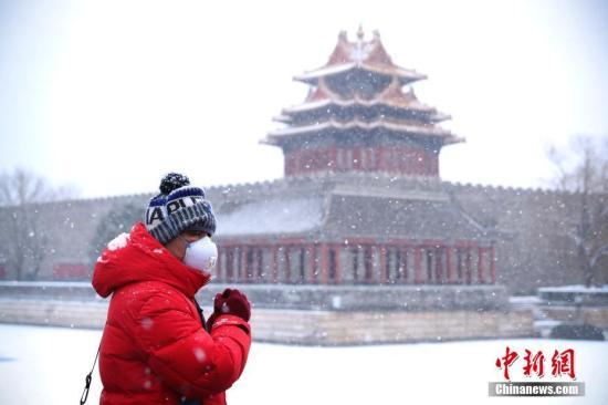 资料图:北京故宫角楼旁,民众戴着口罩出行。中新社记者 刘震 摄