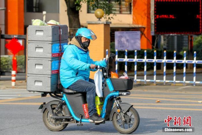 资料图:2月5日,湖北武汉经济技术开发区,一名送货的配送员正在忙碌工作。中新社记者 张畅 摄