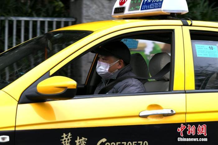 资料图:正在路上营运的出租车司机。中新社记者 王东明 摄