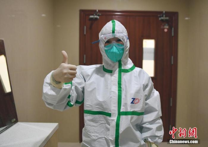 新型冠状病毒感染的肺炎疫情发生以来,浙江医院肩负起收治疑似病人的工作。在隔离区内每天有两名医生,一名负责白班一名24小时在岗;护士则三班倒工作,每个班配置2名护士,一个在感染区工作一个在办公区工作。医护人员在隔离衣、防护服、口罩、护目镜的层层防护下,连续8个多小时不吃不喝。每当脱下护目镜和口罩,每个人的脸上都留下了深深的勒痕。他们奋战在距离肺炎病毒最近的地方,书写着抗击新冠肺炎动人故事。图为医护人员穿好防护服自信地竖起大拇指。 李晨韵 摄